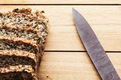 Knife and wholemeal, wholewheat bread on wooden table. Organic, healthy food - stock photo