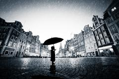 Child with umbrella standing alone on cobblestone old town in rain - stock illustration
