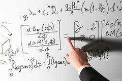 Teacher pointing finger on equality math symbol on whiteboard. Mathematics an - stock photo