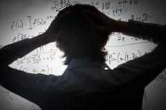 Student holding his head looking at complex math formulas on whiteboard. Math Stock Photos