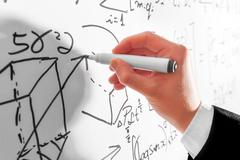 Man writing complex math formulas on whiteboard. Mathematics and science Stock Photos