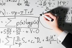 Man writing complex math formulas on whiteboard. Mathematics and science - stock photo