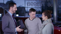 4K Couple in car dealership with salesman shake hands on a deal to buy new car - stock footage