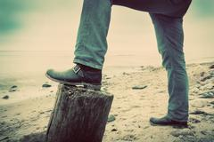 Man in jeans and elegant shoes leaning against tree trunk on wild beach looki Stock Photos