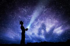 Man in hat throwing light beam up the night sky full of stars. Conceptual - e - stock illustration