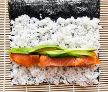 Preparing sushi background. Salmon, avocado, rice on seaweed. - stock photo