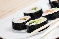 Sushi with salmon, avocado, rice in seaweed and chopsticks on a plate. - stock photo