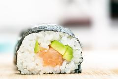 Sushi with salmon, avocado, rice in seaweed and chopsticks on wooden table - stock photo
