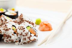 Sushi with salmon, avocado, rice in seaweed served with wasabi and ginger. - stock photo