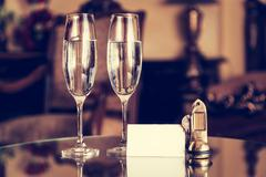Full champagne glasses, antique keys and blank white card. Luxury hotel apart - stock photo