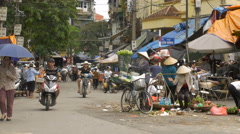 A busy street in Vietnam with traffic, pedestrians, flowers, and bicycles. Stock Footage
