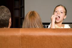 Girl eating popcorn with family Stock Photos