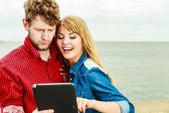 Young couple with tablet by seaside outdoor Stock Photos
