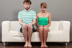Shy woman and man sitting close to each other on couch. - stock photo