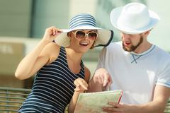 Stock Photo of Tourist couple in city looking up directions on map