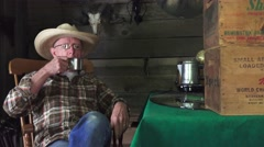Cowboy in the bunkhouse, sitting in rocking chair and enjoying hot coffee Stock Footage