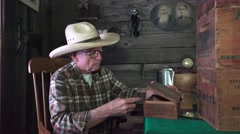 Cowboy in the bunkhouse, small wooden cigar box Stock Footage