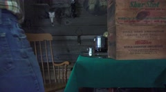Cowboy in the bunkhouse, man walks up to the coffee pot and pours Stock Footage