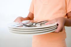 Boy holding plates and cutlery - stock photo