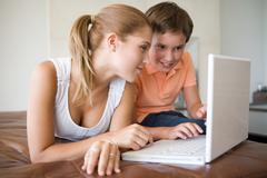 Brother and sister using laptop - stock photo