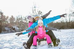 Family sitting on a sleigh on a beautiful snowy day Stock Photos