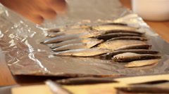 Chef puts fresh anchovy in a row at aluminum foil prior foil cooking; close up Stock Footage