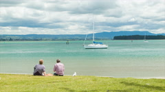 Tauranga Older Couple Sitting on Grass Viewing Over the Harbour Stock Footage
