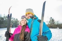 Couple holding skis on a beautiful snowy day Stock Photos