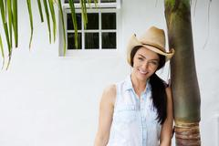 Smiling woman with cowboy hat leaning against tree Stock Photos