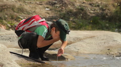 Little explorer drink water from the river 2 - stock footage