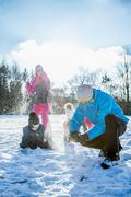 Family playing snowball fight on a beautiful snowy day Kuvituskuvat