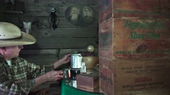 Cowboy in the bunkhouse, pours coffee and adds booze Stock Footage