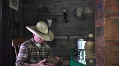 Cowboy in the bunkhouse, man opens old cigar box Stock Footage