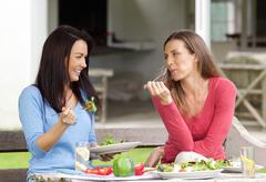 Two female friends enjoying lunch together - stock photo