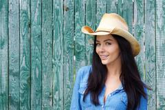 Close up smiling woman wearing cowboy hat - stock photo