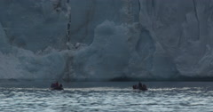 Two rafts with tourists motors away from glacier wall when glacier calves Stock Footage