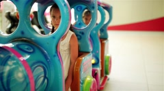 Two beautiful little girls ride small train toy Stock Footage