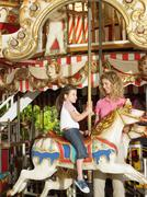 Mother and daughter on carousel Stock Photos