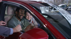 4K Happy couple in car dealership take key to new car from salesman Arkistovideo