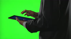 Young businessman using a tablet pc in a virtual business environment on gree Stock Footage