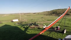 A farm yard with equipment and wind turbines in the background Stock Footage