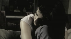 Sad lonely girl sitting on bed feeling heart broken slow motion closeup Stock Footage