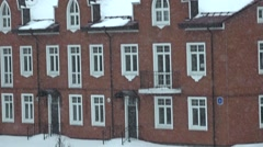 Vertical pan: snow against red brick townhouses super slow motion video - stock footage