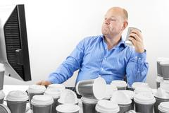 Hardworking business man drinks too much coffee Stock Photos