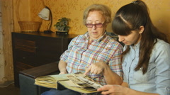 Old and young woman looking at family photo album on sofa at home Stock Footage