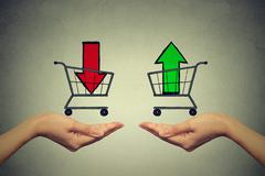 Buy or cell concept. Stock market trading. Two hands with consumer baskets - stock photo