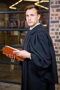 Lawyer standing near library with law book - stock photo