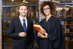 Businessman standing with lawyer near library Stock Photos
