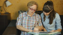 Old and young woman looking at family photo album on sofa at home - stock footage