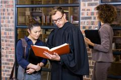 Lawyer and businesswoman reading law book - stock photo